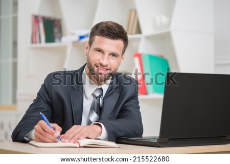 Close-up portrait of handsome confident businessman sitting at the table in office interior and attentively writing some notes in red notebook and looking at the camera with happy smile - stock photo