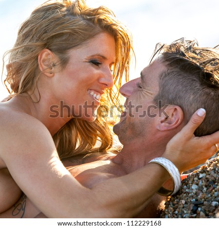 Close up portrait of handsome couple on beach about to kiss.