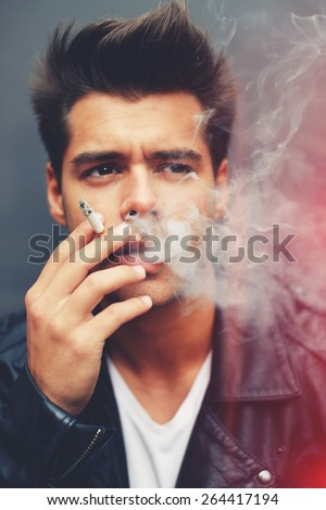Close up portrait of handsome fashion man exhaling cigarette smoke while looking away, trendy attractive man blowing smoke out of his mouth standing on grey background, filtered image, red flare light - stock photo