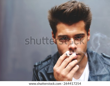 Close up portrait of handsome fashionable man exhaling cigarette smoke while looking to the camera, trendy attractive man blowing smoke out of his mouth standing on grey background, filtered image - stock photo