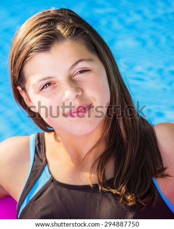 Close-up portrait of handsome girl in a swimming pool - stock photo
