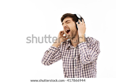 Close-up portrait of handsome romantic young blue-eyed dark-haired man wearing casual plaid shirt singing in head phones. Emotional happy face. Isolated. - stock photo