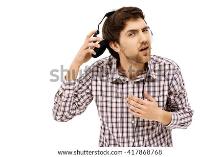 Close-up portrait of handsome romantic young blue-eyed dark-haired man wearing casual plaid shirt in head phones. Emotional surprised face. Isolated. - stock photo