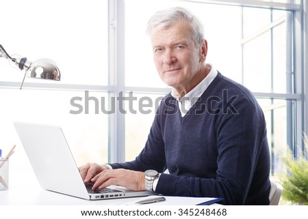 Close-up portrait of handsome senior businessman using a laptop while looking at camera.