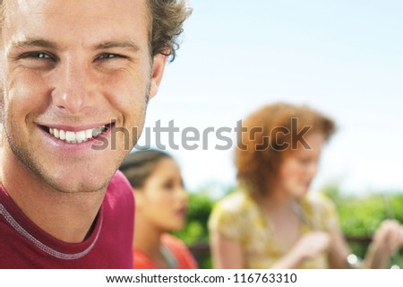 Close up portrait of handsome smiling man with his friends behind him - selective focus