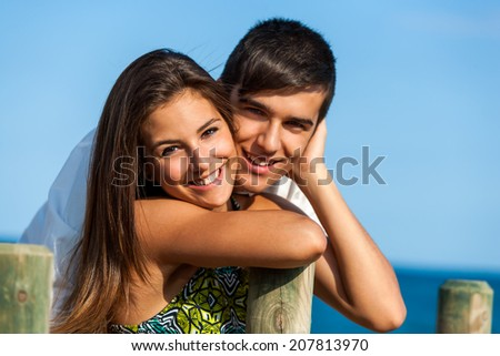 Close up portrait of handsome teen couple at sea side. - stock photo