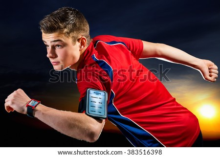 Close up portrait of handsome teen sports man with activity app on digital devices. Young man wearing armband with smart phone and smart watch against sunset background. - stock photo