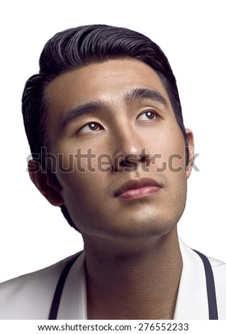 Close-up portrait of handsome young Chinese man wearing black and white suit and looking up. Color image.