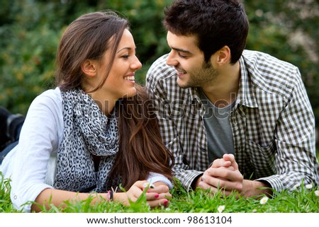 Close up portrait of handsome young couple laying on grass outdoors. - stock photo