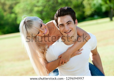 Close up portrait of handsome young couple piggybacking in sunny park.