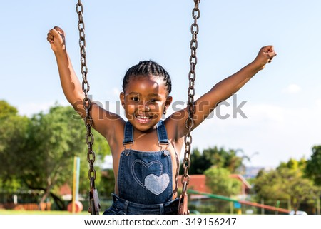 Close up portrait of Happy African kid raising arms on swing in park.