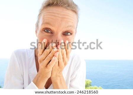 Close up portrait of happy and joyful woman with a fun expression of joy against a blue sky background using her hands to cover her mouth. Feelings and emotions in lifestyle. Gestures and expressions. - stock photo