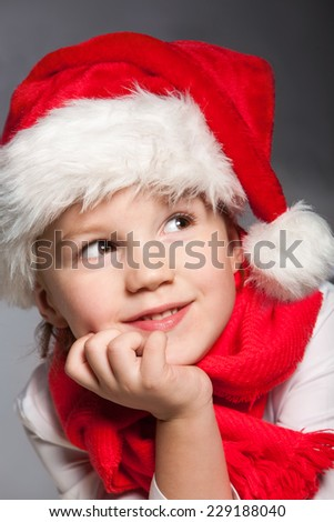 Close-up portrait of happy boy in Santa hat on gray background