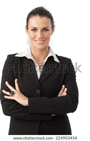 Close up portrait of happy brunette caucasian businesswoman wearing suit, standing in front of white background. Looking at camera, arms crossed, smiling. - stock photo