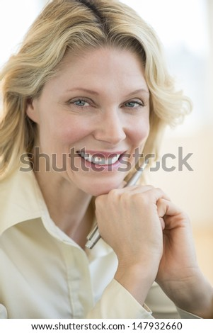 Close-up portrait of happy businesswoman with hand on chin in office - stock photo