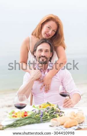 Close-up portrait of happy couple relaxing in the cafe. Red-haired woman hugging her husband isolated on sea.