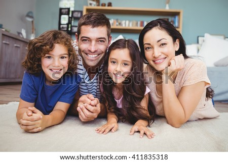 Close-up portrait of happy family lying on carpet at home - stock photo