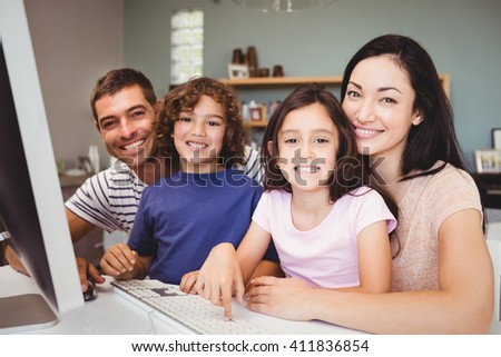 Close-up portrait of happy family sitting by computer at home - stock photo
