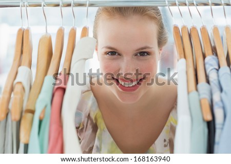 Close-up portrait of happy female customer amid clothes rack