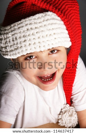Close-up portrait of happy joyful beautiful little boy in hat of Santa Claus, studio shot