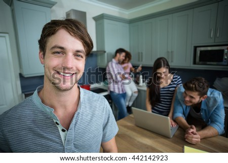 Close-up portrait of happy man with friends in background at home