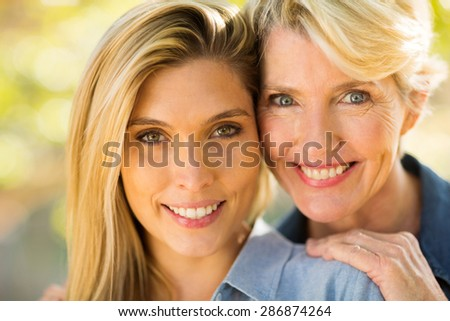 close up portrait of happy mother and daughter - stock photo