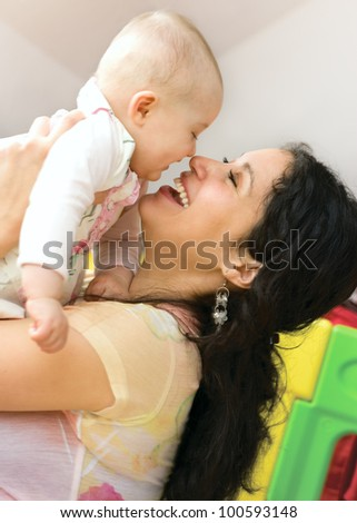 Close-up portrait of happy mother holding her baby in hands - stock photo