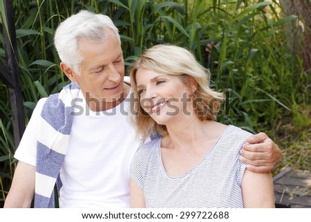 Close-up portrait of happy senior couple sitting at the lakeside. Elderly man hugs his wife while relaxing at nature.  - stock photo