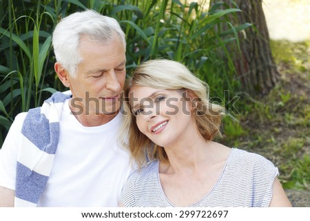 Close-up portrait of happy senior couple sitting at the lakeside. Elderly man hugs his wife while relaxing at nature.