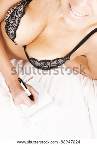 close up portrait of happy sexy woman taking notes - stock photo