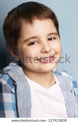 Close-up portrait of happy smiling beautiful little boy, studio shot - stock photo