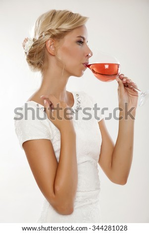 Close up portrait of happy smiling beauty young adult attractive sexy and sensuality pretty blonde woman with glass of red rose wine, in white dress isolated on white background - stock photo