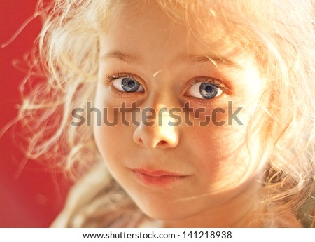 Close up portrait of happy smiling caucasian five years old blond child girl on a red background - sunset light - stock photo