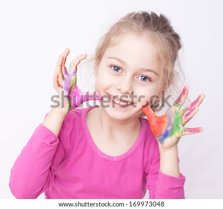 Close up portrait of happy smiling caucasian five years old blond child girl with colorful painted hands on a white background - careless childhood - stock photo