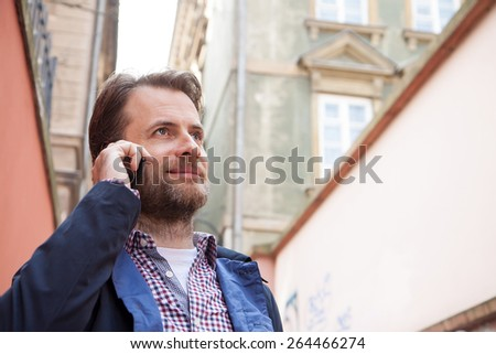 Close up portrait of happy smiling forty years old caucasian man in casual clothes talking on a mobile phone. Old city buildings as background. - stock photo