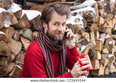 Close up portrait of happy smiling forty years old caucasian man talking on a mobile phone and drinking hot tea outdoor countryside during winter  - stock photo