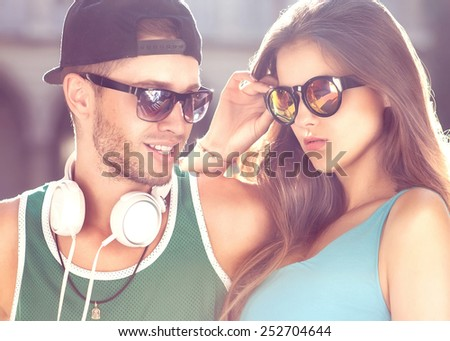 Close up portrait of happy smiling hipster couple in love. Wearing retro clothes and sunglasses. Fashion. Vogue.  - stock photo