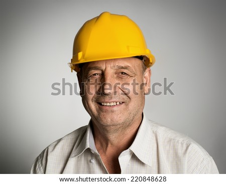Close up portrait of happy smiling mature engineer or builder in yellow hardhat posing in studio.  - stock photo
