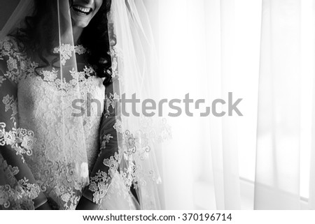 Close up portrait of happy stylish brunette bride under the veil in luxury white dress standing near the window