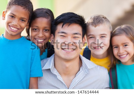 close up portrait of happy teacher with primary school students