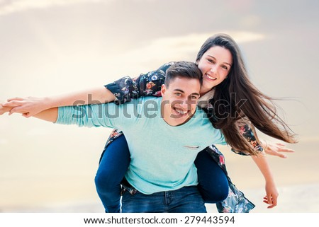 Close up portrait of happy teen couple playing around outdoors. Boy piggybacking girlfriend. - stock photo