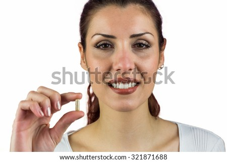Close-up portrait of happy woman holding pill against white background - stock photo