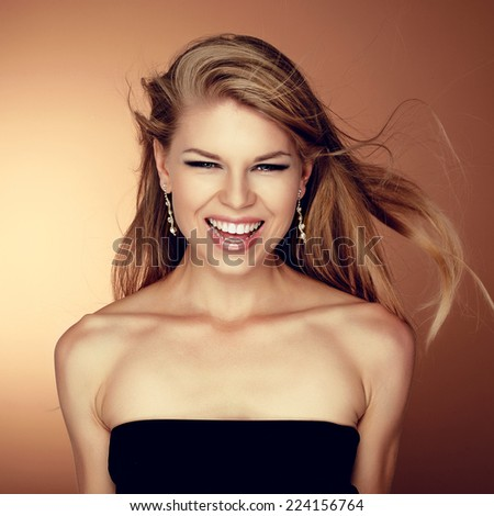 Close up portrait of happy woman with toothy smile winning success. Young lovely funky Caucasian girl laughing with flying hair.   - stock photo