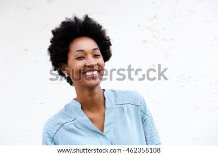 Close up portrait of happy young african woman standing against white wall