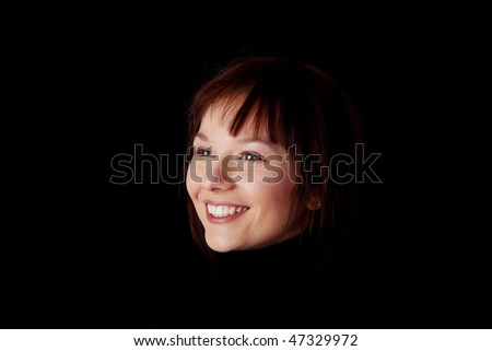 Close up portrait of happy young caucasian woman isolated on black background - stock photo