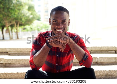 Close up portrait of happy young guy sitting outdoors on steps