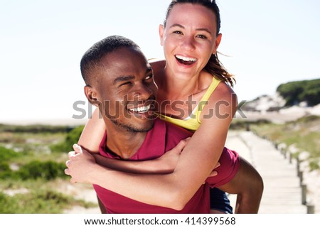 Close up portrait of happy young man carrying attractive girlfriend on his back - stock photo
