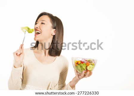 Close up portrait of happy young woman eating vegetables salad, studio shot on white background. Healthy food concept. Skin care and beauty.