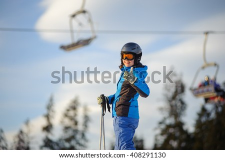 Close-up portrait of happy young woman skier at ski resort against ski-lift in the evening. Girl is standing on a ski slope and giving the thumb up. Winter vacation. - stock photo