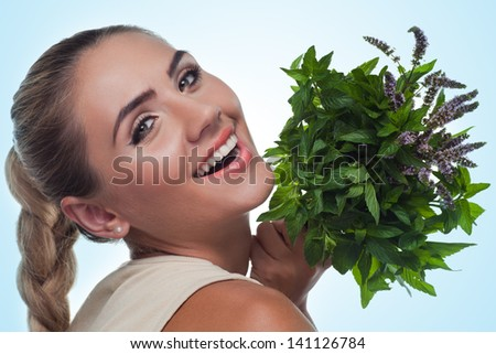 Close-up portrait of happy young woman with a bundle of fresh mint. Concept vegetarian dieting - healthy food - stock photo